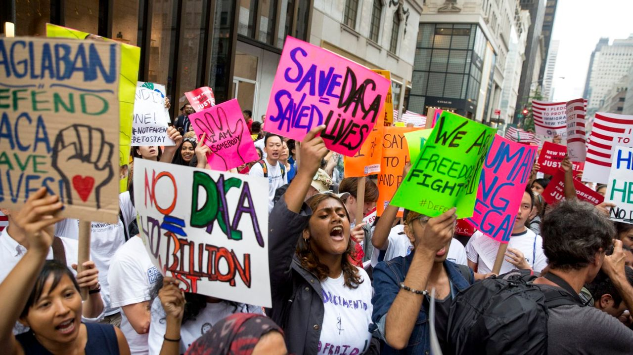 Protesters+hold+signs+to+help+keep+DACA+program.+