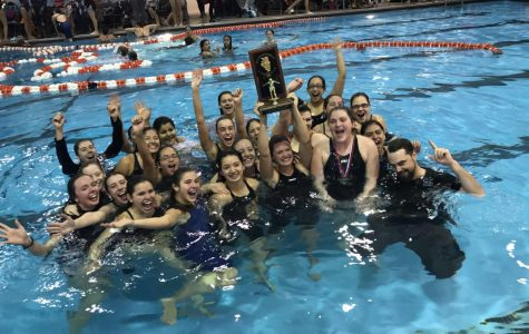 Oak Lawn Swimmers Jump into Joy as they win conference at Evergreen High School. Ellie Featherstone Hold the trophy of victory along with other spartan swimmers.