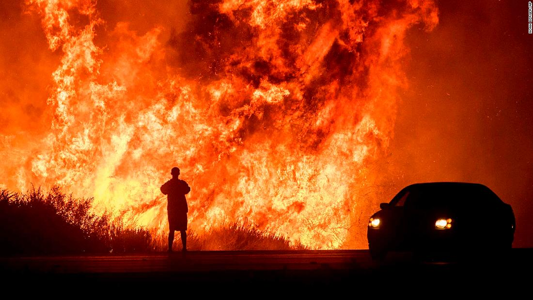 Someone watches flames from the California fire lburn everything in its path.