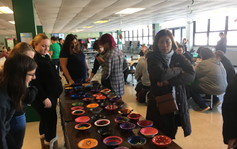 A group of fundraiser attendees surveys the handmade bowls for purchase
