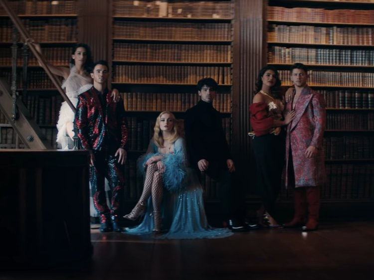 "A screen cap from the ""Sucker"" music video, featuring the three brothers ad their wives."