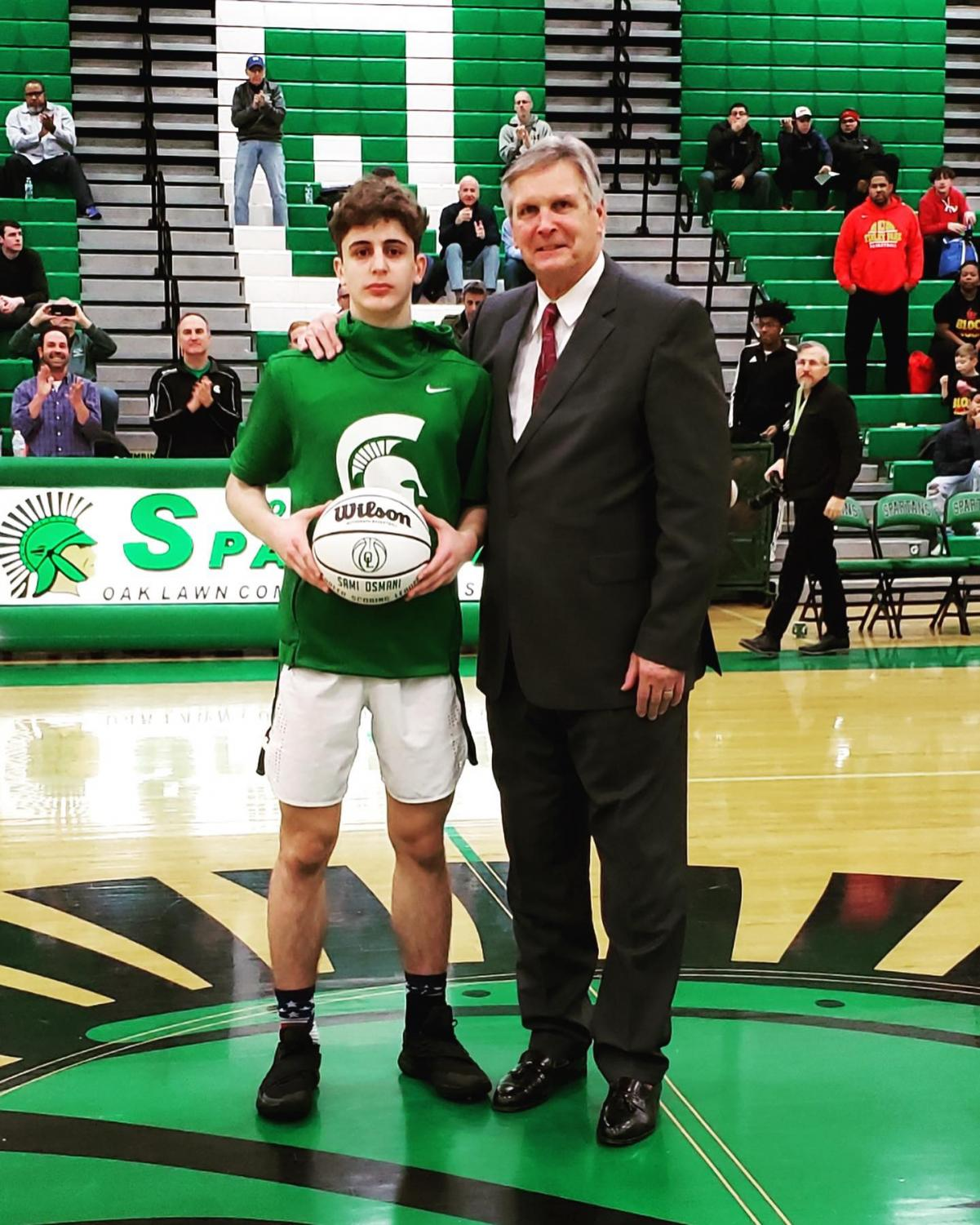 Senior point guard, Sami Osmani, being commemorated by former NBA player CJ Kupec. Sami surpassed Kupec's scoring record of 1,377 points in a landslide victory over Bremen High School.